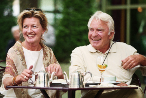 Mature couple sitting in street cafe