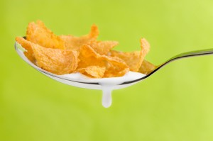 spoon with corn flakes on green background
