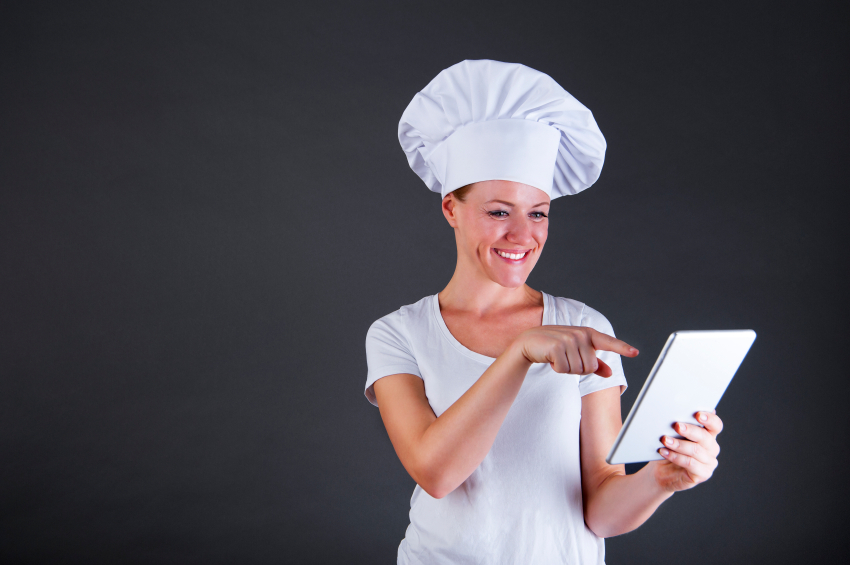 woman chef with tablet over dark background