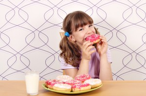hungry little girl eating sweet donuts zucchero per i bambini