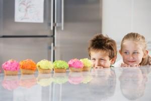 Siblings Peeking Over Counter At Row Of Cupcakes