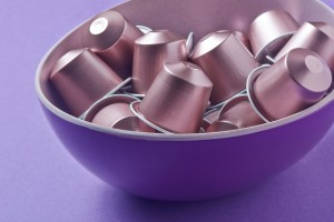 Pink Coffee capsules on lilac background