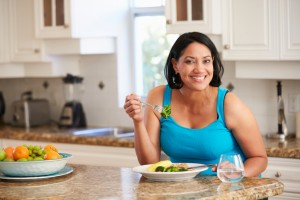 Overweight Woman Eating Healthy Meal in Kitchen metabolismo