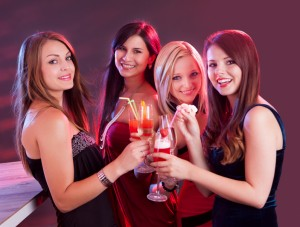 Happy female friends celebrating energy drink alcolici