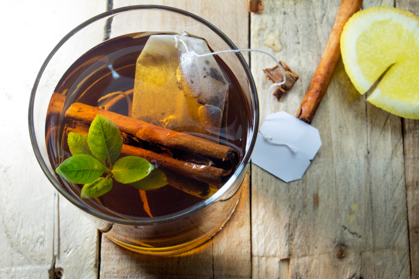 healthy cup of hot tea on wooden background, lemon and cinnamon