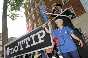 12/07/2014 - Protests against the EU-US trade deal (TTIP - Transatlantic Trade and Investment Partnership) outside Europe House, the London Headquarters of the European Commission and the European Parliament, in Smith Square, London. A puppeteer on stilts with a 'puppet' dressed as an NHS nurse to highlight the threat the deal poses to public services like the NHS.