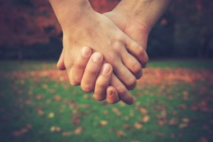 Close up on a couple holding hands in the park in autumn
