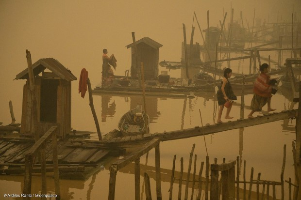 Members of the indigenous community live at the riverbanks in Kapuas river where the air is engulfed with thick haze at Sei Ahass village, Kapuas district, Central Kalimantan province on Borneo island, Indonesia. These fires are a threat to the health of millions. Smoke from landscape fires kills an estimated 110,000 people every year across Southeast Asia, mostly as a result of heart and lung problems, and weakening newborn babies.