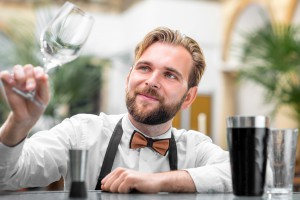 Elegant barman checking the cleanliness of glass at the restaurant