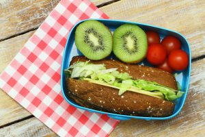Healthy lunch consisting of brown cheese and lettuce roll, cherry tomatoes and kiwi fruit