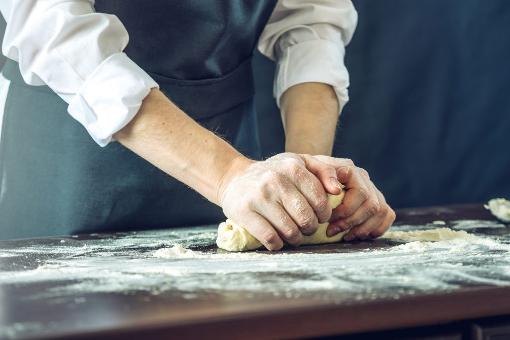 The chef in black apron makes pizza dough with your hands on the table